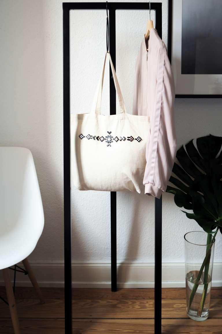 Moderne Ideen mit Bügelperlen: Stylischer Jutebeutel an schwarzer Garderobe